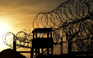 This photo made during an escorted visit and reviewed by the US military, shows the razor wire-topped fence and a watch tower at the abandoned